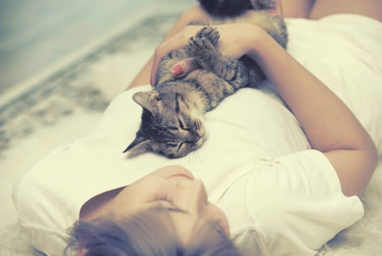 Cat sleep on woman chest on carpet.