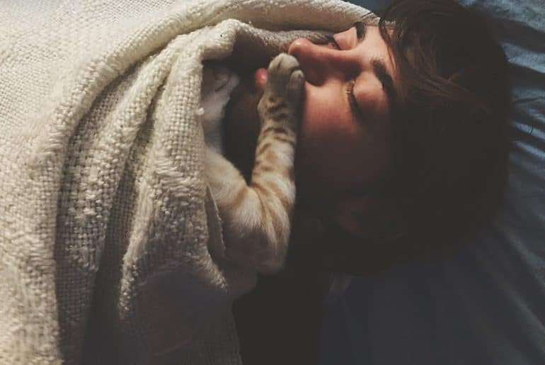 Cat putting paw on owner's face at night