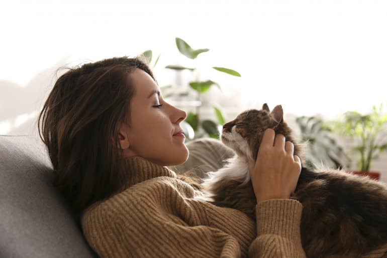 Portrait of young woman holding cute siberian cat